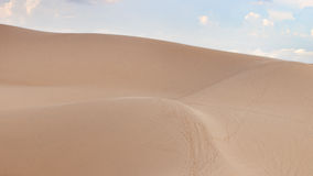 Abandonnez les dunes de paysage pendant l'après-midi avec des nuages de blanc de cieux bleus Images libres de droits
