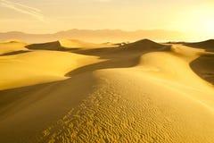 Abandonnez les dunes de sable avec la lumière d'or Photo libre de droits