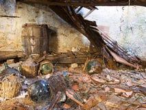Abandono, propiedad abandonada destartalada, sótano con las damajuanas Imágenes de archivo libres de regalías
