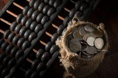 Abaque avec des pièces de monnaie dans le sac à jute Photographie stock libre de droits