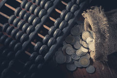 Abaque avec des pièces de monnaie dans le sac à jute Images stock