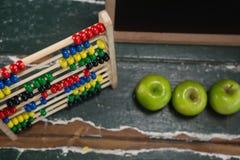 Abaque et pommes vertes sur la table en bois Image stock