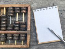 Abaque sur le fond en bois avec l'espace sur le carnet et le stylo blancs Photos libres de droits