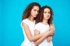 Abarcamiento de dos gemelos de las muchachas, mirando la cámara sobre fondo azul Foto de archivo