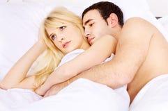 Abarcamiento de ella en cama Foto de archivo libre de regalías