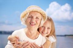 Abarcamiento de la abuela feliz y de la nieta que miran la leva Foto de archivo