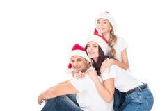 Abarcamiento de la familia en los sombreros de Papá Noel Foto de archivo