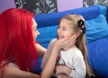 Abarcamiento de la hija cariñosa feliz de la madre y de la sonrisa Fotos de archivo libres de regalías