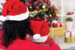 Abarcamiento de la mamá y del hijo, mirando el árbol de navidad, tiro de Fotos de archivo