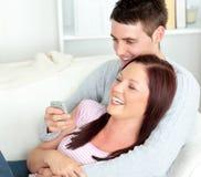 Abarcamiento de la televisión de observación de los pares en el sofá Fotografía de archivo libre de regalías