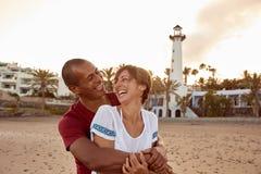 Abarcamiento de los pares adultos que presentan en la playa Imagen de archivo