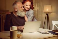 Abarcamiento de los pares envejecidos centro que se sientan cerca del ordenador portátil Imagen de archivo libre de regalías