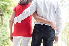 Abarcamiento de los pares que caminan en un parque Imágenes de archivo libres de regalías