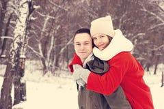 Abarcamiento de los pares que miran la cámara con sonrisas en parque del invierno Fotos de archivo libres de regalías