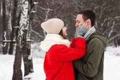Abarcamiento de los pares que miran la cámara con sonrisas en parque del invierno Imagen de archivo libre de regalías
