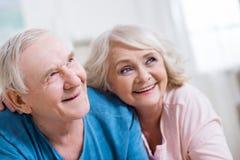 Abarcamiento de mentira de los pares mayores y mirada lejos en casa Fotografía de archivo