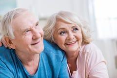 Abarcamiento de mentira de los pares mayores y mirada lejos en casa Imagen de archivo