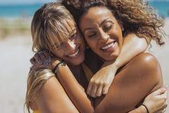 Abarcamiento de mujeres diversas felices en la playa Imágenes de archivo libres de regalías