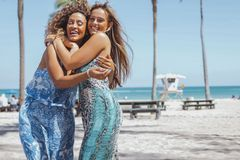 Abarcamiento de mujeres felices en la playa Imágenes de archivo libres de regalías