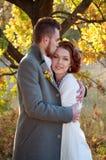 Abarcamiento de novia y del novio Ajuste al aire libre del otoño romántico Foto de archivo libre de regalías