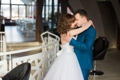 Abarcamiento de novia y del novio del cierre-uphappy cara a cara en el interior moderno del restaurante Imagen de archivo
