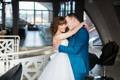 Abarcamiento de novia y del novio del cierre-uphappy cara a cara en el interior moderno del restaurante Foto de archivo
