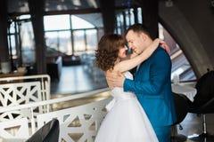Abarcamiento de novia y del novio del cierre-uphappy cara a cara en el interior moderno del restaurante Fotografía de archivo