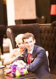 Abarcamiento de novia y del novio Recienes casados que se sientan en el sofá en café y el abarcamiento Fotografía de archivo