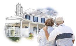 Abarcamiento de pares mayores sobre el dibujo de la casa y de la foto en blanco Foto de archivo libre de regalías