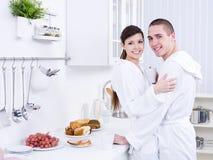 Abarcamiento de pares sonrientes en la cocina Foto de archivo libre de regalías