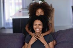 Abarcamiento de risa africano alegre de la hija de la mamá y del niño en casa imágenes de archivo libres de regalías