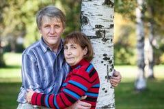 Abarcamiento del marido maduro y de la esposa que se colocan al lado de árbol en parque Fotografía de archivo libre de regalías