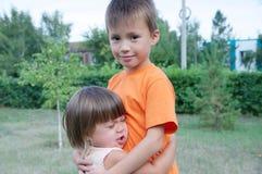 Abarcamiento del muchacho y de la niña Hermanos felices Fotografía de archivo