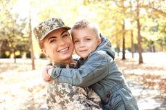 Abarcamiento del soldado y del niño de la madre Fotografía de archivo