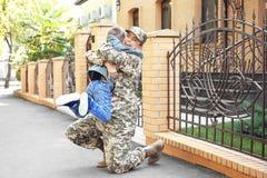 Abarcamiento del soldado y del niño de la madre Imagenes de archivo