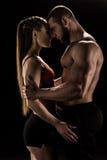 Abarcamiento deportivo sensual de los pares aislado en negro Fotografía de archivo