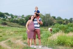 Abarcamiento embarazada feliz de la familia Fotos de archivo