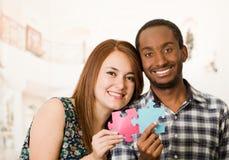 Abarcamiento encantador interracial de los pares amistoso, soporte de pedazos grandes del rompecabezas y feliz el obrar recíproca Fotos de archivo libres de regalías