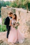 Abarcamiento feliz de los recienes casados El hombre en smoking y mujer en un vestido de boda rosado está presentando en la natur Fotos de archivo libres de regalías