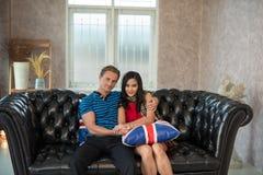 Abarcamiento joven de dos amantes, sentándose en el sofá Fotografía de archivo