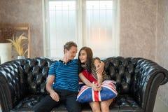 Abarcamiento joven de dos amantes, sentándose en el sofá Imágenes de archivo libres de regalías