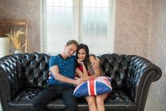 Abarcamiento joven de dos amantes, sentándose en el sofá Fotos de archivo
