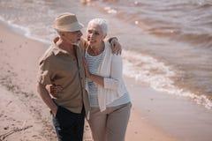 Abarcamiento que camina de los pares mayores en la playa arenosa Imagen de archivo