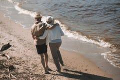 Abarcamiento que camina de los pares mayores en la playa arenosa Imágenes de archivo libres de regalías