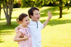 Abarcamiento que camina feliz de los pequeños niños en verano Imagenes de archivo