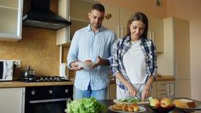 Abarcamiento que se besa de los pares jovenes felices y charla en la cocina mientras que cocina el desayuno en casa Fotografía de archivo