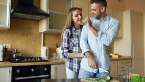 Abarcamiento que se besa de los pares jovenes felices y charla en la cocina mientras que cocina el desayuno en casa Foto de archivo
