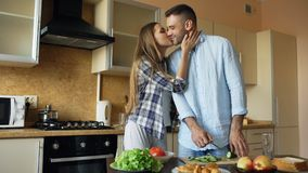 Abarcamiento que se besa de los pares jovenes felices y charla en la cocina mientras que cocina el desayuno en casa Imagen de archivo libre de regalías