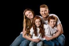 Abarcamiento que se sienta de la familia feliz del pelirrojo y sonrisa en la cámara Foto de archivo libre de regalías