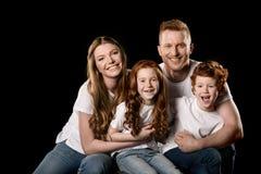 Abarcamiento que se sienta de la familia feliz del pelirrojo y sonrisa en la cámara Fotografía de archivo libre de regalías